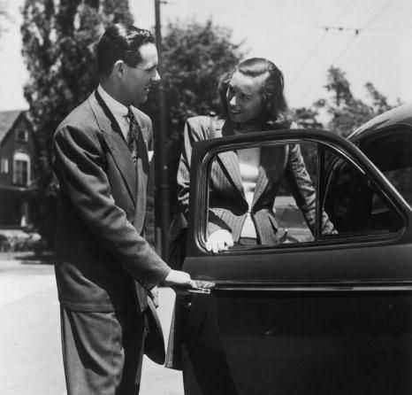 black and white photo of man opening car door for woman